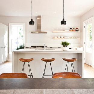 Mittelgroße Moderne Wohnküche in U-Form mit Unterbauwaschbecken, weißen Schränken, Küchenrückwand in Weiß, Küchengeräten aus Edelstahl, hellem Holzboden und Kücheninsel in New York
