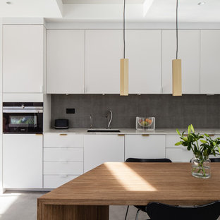 Inspiration for a contemporary single-wall kitchen/diner in London with a submerged sink, flat-panel cabinets, white cabinets, grey splashback, stainless steel appliances, concrete flooring, no island, grey floors and white worktops.