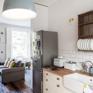 ロンドンの小さいトラディショナルスタイルのおしゃれなキッチン (エプロンフロントシンク、フラットパネル扉のキャビネット、白いキャビネット、木材カウンター、白いキッチンパネル、サブウェイタイルのキッチンパネル、シルバーの調理設備、無垢フローリング) の写真