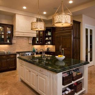 他の地域の大きいエクレクティックスタイルのおしゃれなキッチン (レイズドパネル扉のキャビネット、濃色木目調キャビネット、ベージュキッチンパネル、ボーダータイルのキッチンパネル、アンダーカウンターシンク、大理石カウンター、パネルと同色の調理設備、磁器タイルの床) の写真