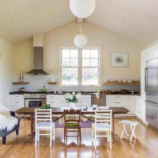 サンフランシスコのカントリー風おしゃれなキッチン (シェーカースタイル扉のキャビネット、白いキャビネット、白いキッチンパネル、サブウェイタイルのキッチンパネル、シルバーの調理設備、無垢フローリング、アイランドなし、黄色い床) の写真
