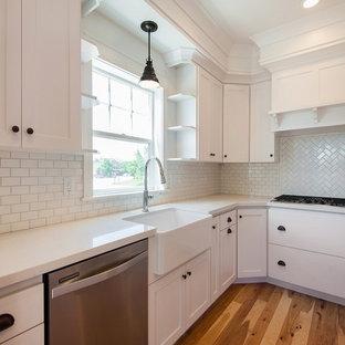 Foto på ett stort amerikanskt u-kök, med en rustik diskho, luckor med infälld panel, vita skåp, vitt stänkskydd, stänkskydd i keramik, rostfria vitvaror och ljust trägolv