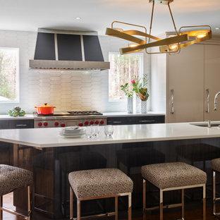 Moderne Küche mit flächenbündigen Schrankfronten, grauen Schränken, Quarzwerkstein-Arbeitsplatte, Küchenrückwand in Weiß, Rückwand aus Porzellanfliesen, Elektrogeräten mit Frontblende, braunem Holzboden und weißer Arbeitsplatte in Boston
