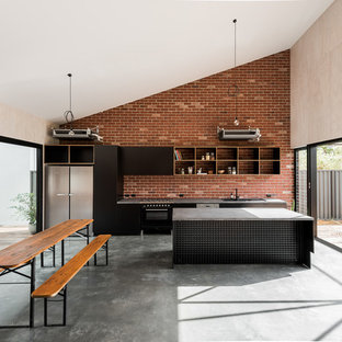 This is an example of an industrial single-wall open plan kitchen in Perth with black cabinets, concrete benchtops, brick splashback, stainless steel appliances, concrete floors, with island, grey floor, flat-panel cabinets and red splashback.