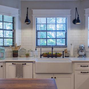 Idées déco pour une cuisine américaine campagne en L de taille moyenne avec un évier de ferme, un placard à porte shaker, des portes de placard blanches, un plan de travail en bois, une crédence grise, une crédence en marbre, un électroménager encastrable, un sol en bois brun, un îlot central, un sol marron et un plan de travail marron.