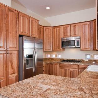 フェニックスの小さいトランジショナルスタイルのおしゃれなキッチン (ダブルシンク、レイズドパネル扉のキャビネット、中間色木目調キャビネット、御影石カウンター、茶色いキッチンパネル、石スラブのキッチンパネル、シルバーの調理設備の、コンクリートの床、赤い床) の写真