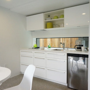 Photo of a modern eat-in kitchen in San Francisco with flat-panel cabinets, white cabinets and stainless steel appliances.