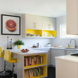 Immagine di una piccola cucina moderna con lavello sottopiano, nessun'anta, ante gialle, top in quarzite, paraspruzzi bianco, paraspruzzi con piastrelle in ceramica, elettrodomestici in acciaio inossidabile, pavimento in cementine, penisola, pavimento nero e top bianco