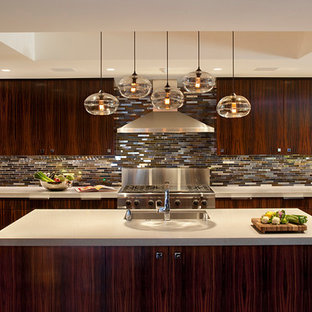 This is an example of a large contemporary u-shaped open plan kitchen in San Francisco with stainless steel appliances, a drop-in sink, flat-panel cabinets, dark wood cabinets, grey splashback, matchstick tile splashback, medium hardwood floors, with island and brown floor.