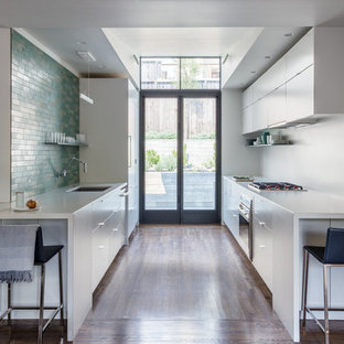 Mid-sized contemporary kitchen designs - Mid-sized trendy galley dark wood floor and brown floor kitchen photo in San Francisco with an undermount sink, flat-panel cabinets, white cabinets, green backsplash, subway tile backsplash, paneled appliances, no island and white countertops