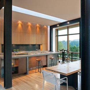 Cette image montre une cuisine américaine parallèle minimaliste avec un placard à porte plane, des portes de placard en bois clair, un évier intégré, une crédence en dalle métallique, un sol en bois clair, un sol beige, un plan de travail en béton, une crédence noire et un plan de travail gris.