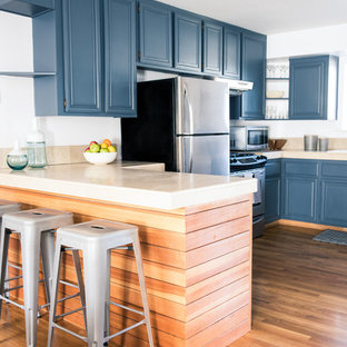 Design ideas for a transitional l-shaped eat-in kitchen in Los Angeles with a double-bowl sink, raised-panel cabinets, blue cabinets, limestone benchtops, beige splashback, stone slab splashback, stainless steel appliances, medium hardwood floors and a peninsula.