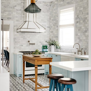 Transitional enclosed kitchen appliance - Example of a transitional u-shaped multicolored floor enclosed kitchen design in San Francisco with a farmhouse sink, shaker cabinets, blue cabinets, gray backsplash, marble backsplash, white appliances, an island and white countertops
