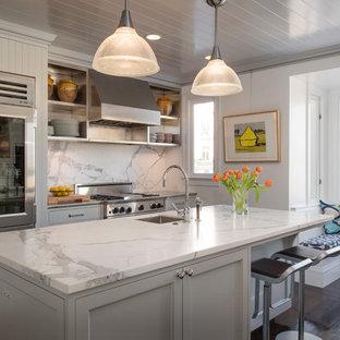 Aménagement d'une cuisine classique avec un électroménager en acier inoxydable, des portes de placard grises, un plan de travail en marbre et une crédence en marbre.