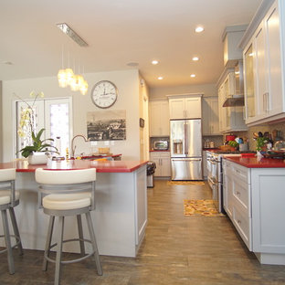 This is an example of a large transitional galley open plan kitchen in Miami with a farmhouse sink, shaker cabinets, grey cabinets, quartzite benchtops, beige splashback, glass tile splashback, stainless steel appliances, porcelain floors, with island, multi-coloured floor and red benchtop.