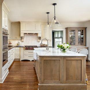 Foto di una cucina a L tradizionale con lavello stile country, ante in stile shaker, ante beige, elettrodomestici in acciaio inossidabile, pavimento in legno massello medio, isola, pavimento marrone e top nero