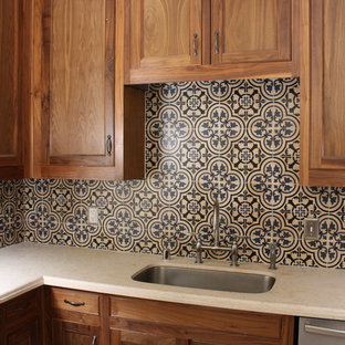 Design ideas for a mediterranean l-shaped eat-in kitchen in Dallas with an undermount sink, recessed-panel cabinets, medium wood cabinets, limestone benchtops, stone tile splashback, stainless steel appliances, travertine floors and with island.