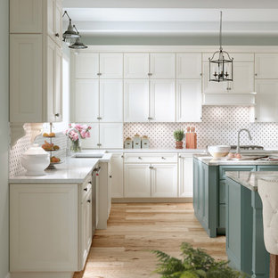 Design ideas for a medium sized traditional galley kitchen/diner in Other with an integrated sink, granite worktops, multi-coloured splashback, ceramic splashback, integrated appliances, light hardwood flooring, multiple islands, recessed-panel cabinets and beige floors.