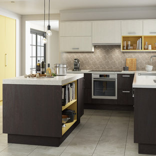 Photo of a mid-sized contemporary l-shaped separate kitchen in Other with an integrated sink, beaded inset cabinets, grey cabinets, granite benchtops, multi-coloured splashback, travertine splashback, stainless steel appliances, ceramic floors, with island and grey floor.