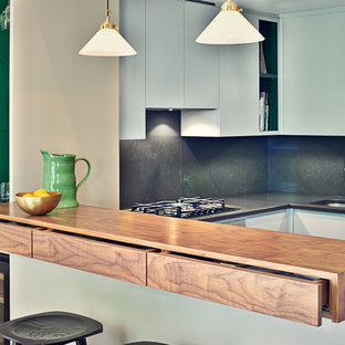 Photo of a small contemporary u-shaped kitchen/diner in London with a breakfast bar.