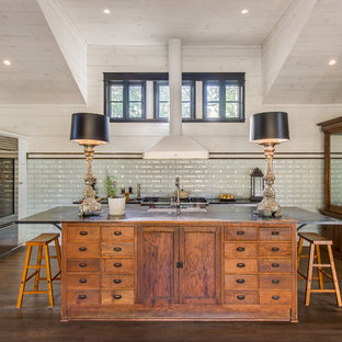 Farmhouse kitchen appliance - Country dark wood floor kitchen photo in Austin with shaker cabinets, white cabinets, white backsplash, subway tile backsplash, stainless steel appliances and an island