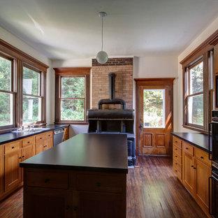 ニューヨークの中サイズのヴィクトリアン調のおしゃれなアイランドキッチン (ドロップインシンク、シェーカースタイル扉のキャビネット、中間色木目調キャビネット、ラミネートカウンター、シルバーの調理設備の、濃色無垢フローリング) の写真