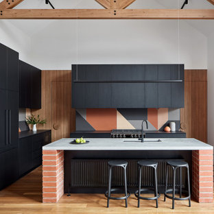 This is an example of a contemporary l-shaped kitchen in Melbourne with flat-panel cabinets, black cabinets, concrete benchtops, terra-cotta splashback, black appliances, medium hardwood floors, with island, black benchtop, an undermount sink, multi-coloured splashback, brown floor and vaulted.