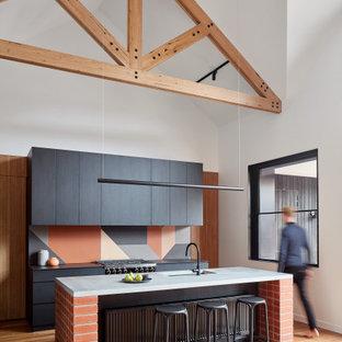 メルボルンのコンテンポラリースタイルのおしゃれなアイランドキッチン (一体型シンク、フラットパネル扉のキャビネット、黒いキャビネット、コンクリートカウンター、テラコッタタイルのキッチンパネル、黒い調理設備、無垢フローリング、黒いキッチンカウンター) の写真