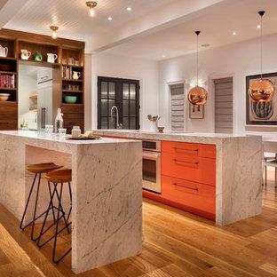Inspiration för moderna vitt kök, med en undermonterad diskho, släta luckor, orange skåp, rostfria vitvaror, mellanmörkt trägolv, flera köksöar och brunt golv