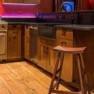 デンバーの中サイズのアジアンスタイルのおしゃれなキッチン (エプロンフロントシンク、シェーカースタイル扉のキャビネット、ソープストーンカウンター、グレーのキッチンパネル、石スラブのキッチンパネル、シルバーの調理設備の、淡色無垢フローリング、濃色木目調キャビネット) の写真