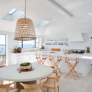 Coastal eat-in kitchen designs - Inspiration for a coastal l-shaped light wood floor and beige floor eat-in kitchen remodel in Orange County with a farmhouse sink, shaker cabinets, white cabinets, white backsplash, paneled appliances, an island and white countertops