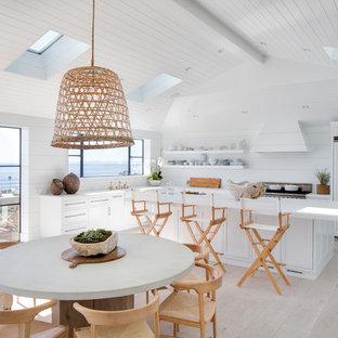 Cette photo montre une cuisine américaine bord de mer en L avec un évier de ferme, un placard à porte shaker, des portes de placard blanches, une crédence blanche, un électroménager encastrable, un sol en bois clair, un îlot central, un sol beige et un plan de travail blanc.