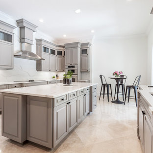 Large contemporary galley separate kitchen in Miami with an undermount sink, louvered cabinets, grey cabinets, quartz benchtops, white splashback, stone slab splashback, stainless steel appliances, marble floors, with island, beige floor and white benchtop.