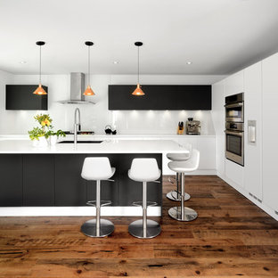 Design ideas for a contemporary kitchen in Toronto with an undermount sink, flat-panel cabinets, black cabinets, white splashback, glass sheet splashback, stainless steel appliances, medium hardwood floors, an island and brown floor.