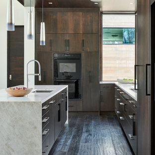 Design ideas for a mid-sized modern u-shaped open plan kitchen in Denver with an undermount sink, flat-panel cabinets, dark wood cabinets, dark hardwood floors, with island, brown floor, limestone benchtops, panelled appliances and white benchtop.