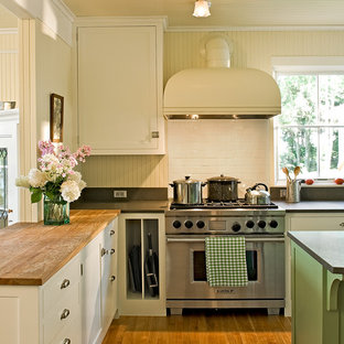 Traditional kitchen ideas - Example of a classic kitchen design in Portland Maine with wood countertops, shaker cabinets, white cabinets, white backsplash, subway tile backsplash and stainless steel appliances