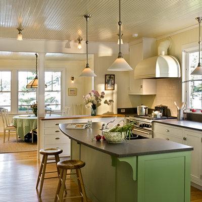 Enclosed kitchen - coastal l-shaped enclosed kitchen idea in Portland Maine with subway tile backsplash, stainless steel appliances, shaker cabinets, white cabinets, granite countertops and white backsplash