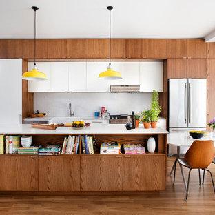 Foto de cocina comedor lineal, retro, con fregadero sobremueble, armarios con paneles lisos, puertas de armario de madera oscura, salpicadero blanco, salpicadero con mosaicos de azulejos, electrodomésticos de acero inoxidable y una isla