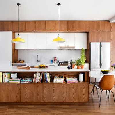 Eat-in kitchen - 1950s single-wall eat-in kitchen idea in Toronto with a farmhouse sink, flat-panel cabinets, medium tone wood cabinets, white backsplash, mosaic tile backsplash, stainless steel appliances and an island