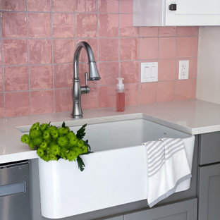 This is an example of a transitional eat-in kitchen in Boston with a farmhouse sink, shaker cabinets, white cabinets, quartz benchtops, pink splashback, ceramic splashback, stainless steel appliances, porcelain floors, with island, white floor and white benchtop.