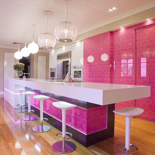 Zweizeilige, Große Moderne Küche mit flächenbündigen Schrankfronten, Quarzwerkstein-Arbeitsplatte, Küchenrückwand in Rosa, Glasrückwand, Küchengeräten aus Edelstahl, hellem Holzboden und Kücheninsel in Los Angeles