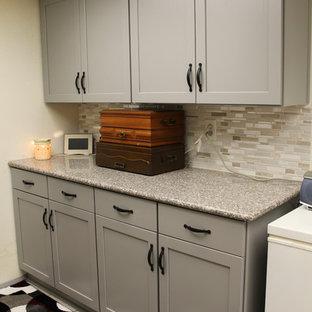 ダラスの小さいトランジショナルスタイルのおしゃれなキッチン (シェーカースタイル扉のキャビネット、グレーのキャビネット、御影石カウンター、マルチカラーのキッチンパネル、ガラス板のキッチンパネル、シルバーの調理設備の、セラミックタイルの床、ピンクの床、ダブルシンク) の写真