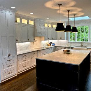 ローリーの大きいエクレクティックスタイルのおしゃれなキッチン (エプロンフロントシンク、シェーカースタイル扉のキャビネット、白いキャビネット、御影石カウンター、白いキッチンパネル、大理石のキッチンパネル、シルバーの調理設備、濃色無垢フローリング、茶色い床、グレーのキッチンカウンター) の写真