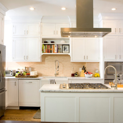 Inspiration for a timeless u-shaped kitchen remodel in New York with stainless steel appliances, a farmhouse sink, shaker cabinets, white cabinets, marble countertops and beige backsplash