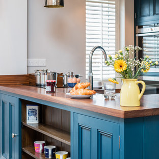 Photo of a small country open plan kitchen in Other with recessed-panel cabinets, blue cabinets, wood worktops, stainless steel appliances and a breakfast bar.