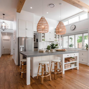 Design ideas for a large beach style l-shaped open plan kitchen in Sunshine Coast with a farmhouse sink, shaker cabinets, white cabinets, marble benchtops, grey splashback, with island, brown floor, grey benchtop, exposed beam and medium hardwood floors.