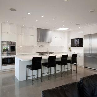 Imagen de cocina en L, moderna, abierta, con electrodomésticos de acero inoxidable, armarios con paneles lisos, puertas de armario blancas, encimera de acrílico, salpicadero blanco, salpicadero de azulejos de cerámica, suelo de cemento y una isla