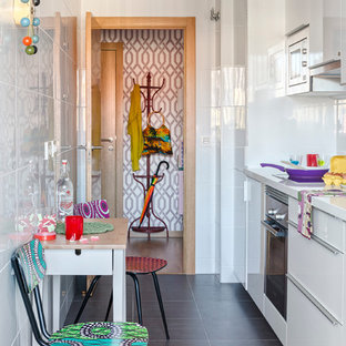 マラガの小さいエクレクティックスタイルのおしゃれなキッチン (フラットパネル扉のキャビネット、白いキャビネット、白いキッチンパネル、シルバーの調理設備の、スレートの床、アイランドなし、人工大理石カウンター) の写真