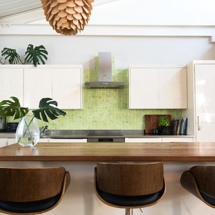 Mid-sized industrial single-wall eat-in kitchen in London with an integrated sink, flat-panel cabinets, white cabinets, stainless steel benchtops, green splashback, ceramic splashback, stainless steel appliances, laminate floors, with island, brown floor and grey benchtop.