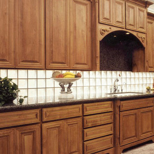Large traditional kitchen designs - Inspiration for a large timeless kitchen remodel in Atlanta with an undermount sink, raised-panel cabinets, medium tone wood cabinets, granite countertops, glass tile backsplash and stainless steel appliances